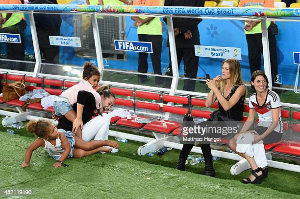 Mandy Capristo, girlfriend of Mesut Oezil, plays with Jerome Boateng of Germany's twin daughters as Sarah Brandner, girlfriend of Bastian...
