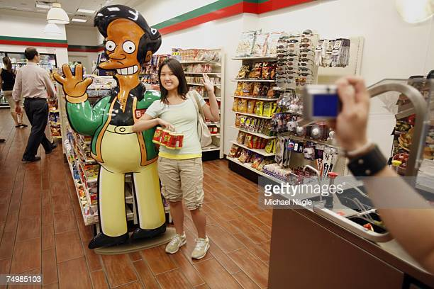 Mandy Lui of Toronto poses with larger than life Apu from the television cartoon show The Simpsons at a 711 store on 345 W 42nd Street converted into...