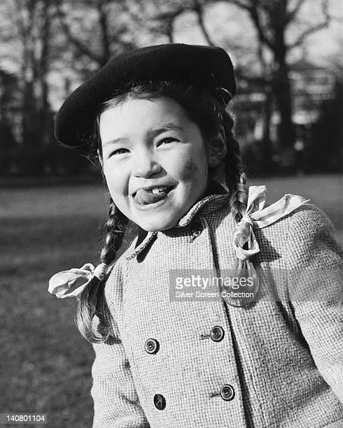 Mandy Miller British child actress wearing a black beret and an overcoat with her hair in pigtails while poking her tongue out circa 1950