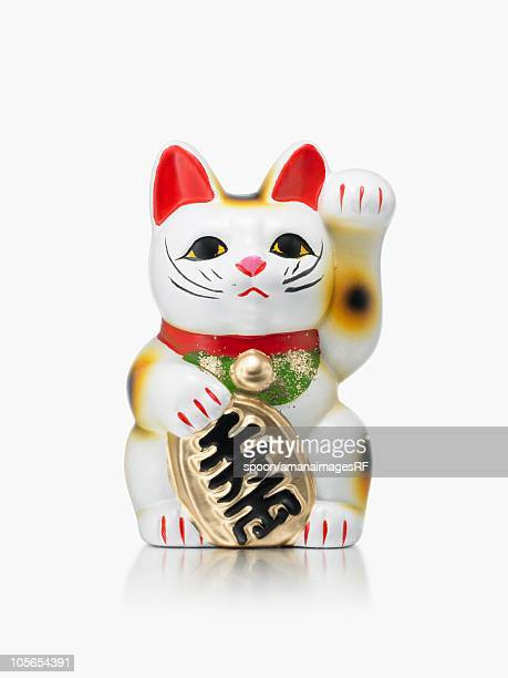 a maneki neko doll on a white background - maneki neko stock photos and pictures
