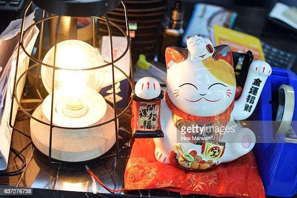 maneki-neko by the cashier - maneki neko stock photos and pictures