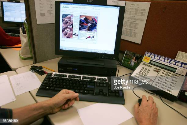 Manfred Bracklow an ecommerce representative sits at his desk as he looks at the online catalog while taking a call from an online customer in the LL...