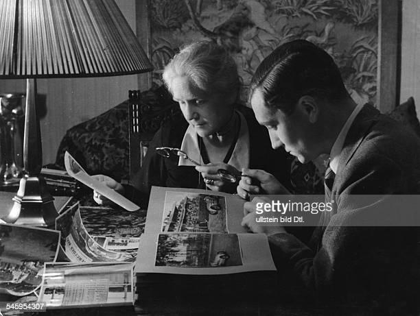 Manfred von Brauchitsch*Sportler Autosport Rennfahrer DMv Brauchitsch und Mutter Olga schauen sich zuhause Fotografien der Rennen an undatierte...