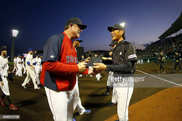 Manger John Farrell of the Boston Red Sox and manager Hiroki Kokubo of Samurai Japan exchange hats before the game at Okinawa Cellular Stadium during...