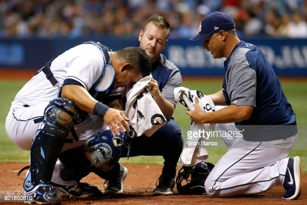 Manger Kevin Cash of the Tampa Bay Rays right and a member of the Rays' medical staff assist catcher Wilson Ramos after Ramos was cut in the head by...
