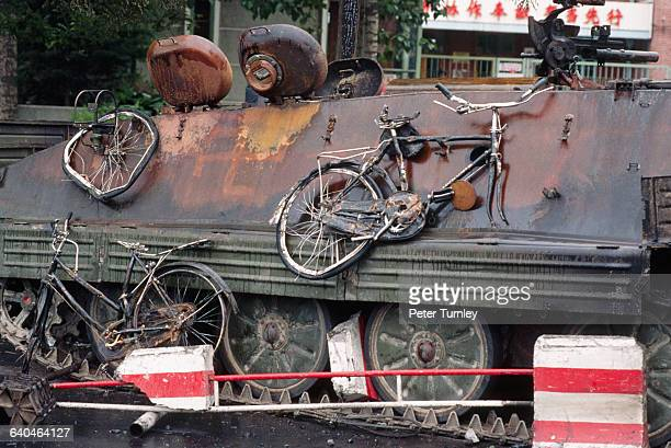 Mangled bicycles hang off the side of a PLA tank which was burned by student protesters in Tiananmen Square