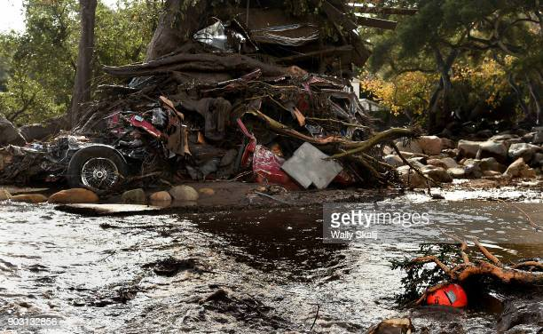 A mangled car along with other debris stack up aguainst a tree along Hot Springs Road in Montecito after a major storm hit the burn area Tuesday...