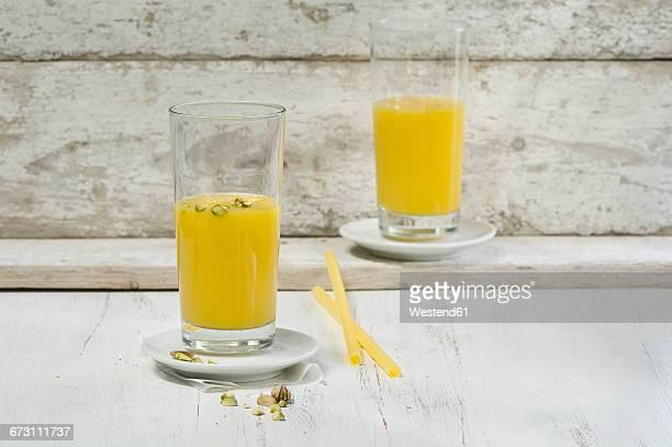 Mango apfel smoothie in glasses, pistachios