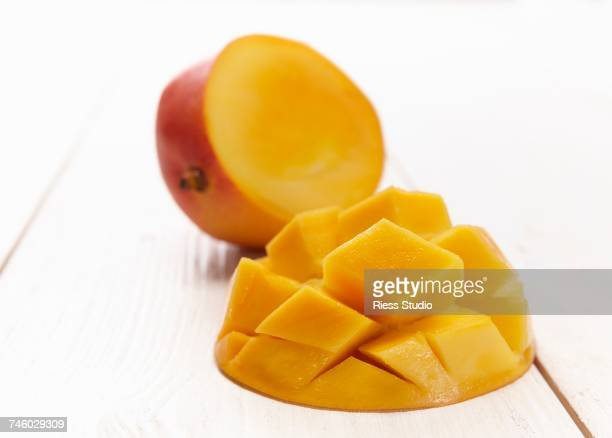 A mango cut in half, with one half cut into chunks in a diamond pattern