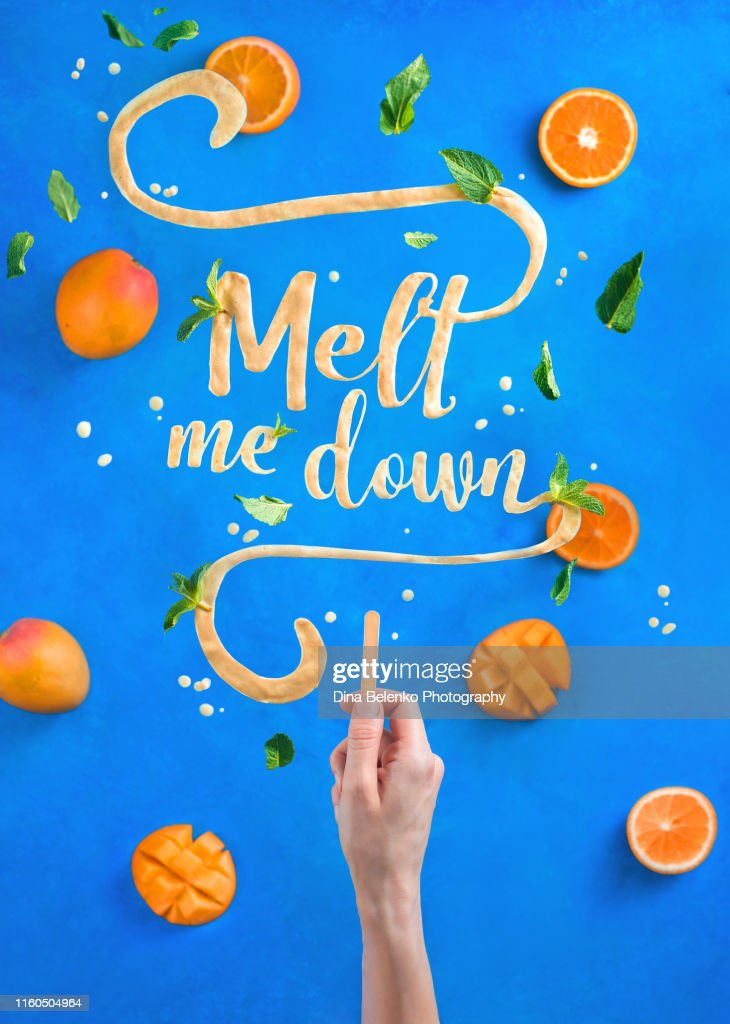 Mango ice cream lettering with popsicle stick spelling Melt Me Down. Creative fruit flat lay with a contrast blue background : Stock Photo
