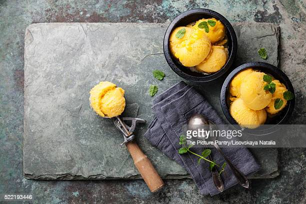Mango ice cream sorbet with mint leaves and Spoon for ice cream