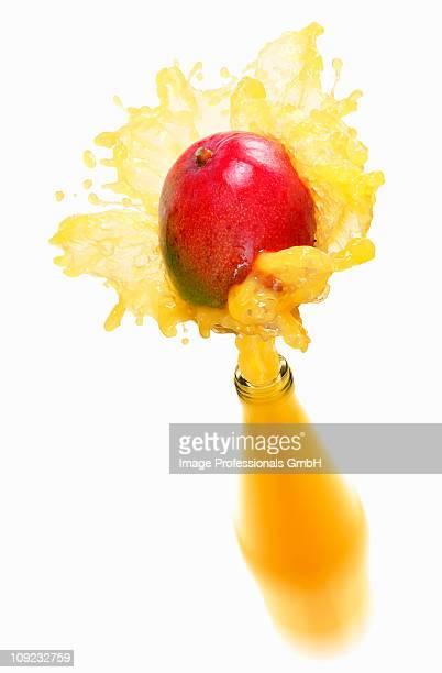 Mango juice splashing out of bottle on mango