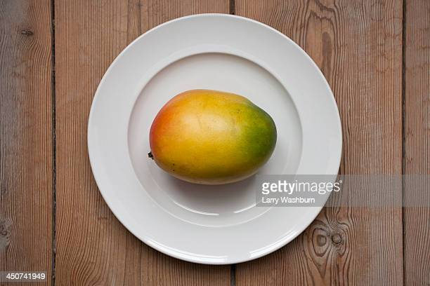 mango on plate laying on wooden table - mango fotografías e imágenes de stock
