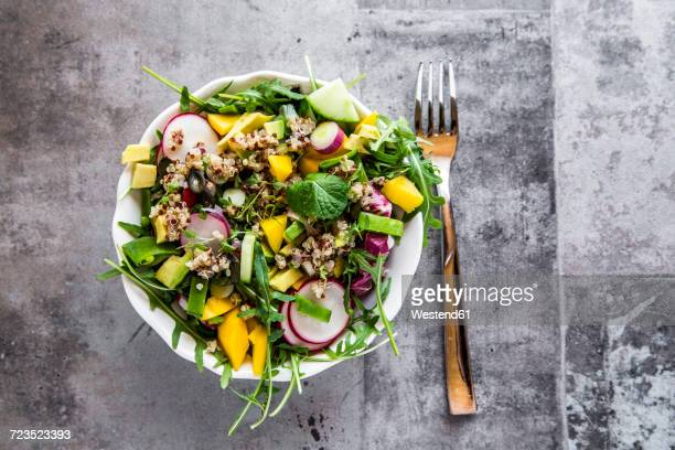 mango quinoa salad with rocket, avocado, cucumber, red radishes and pumpkin seeds - salad stock pictures, royalty-free photos & images