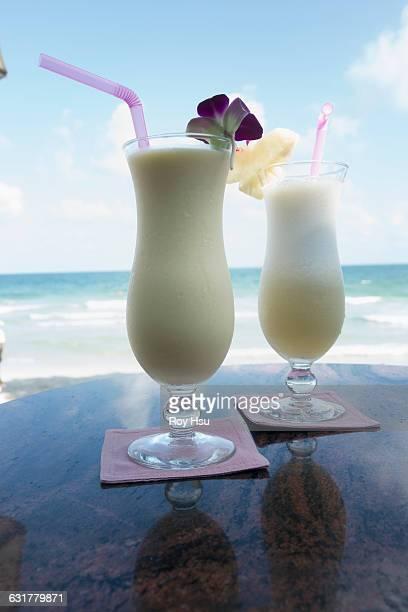 Mango Shake with Pina Colada on table near beach