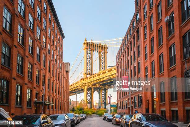 manhattan bridge at sunset seen from dumbo, brookyn, new york city - new york city stock pictures, royalty-free photos & images