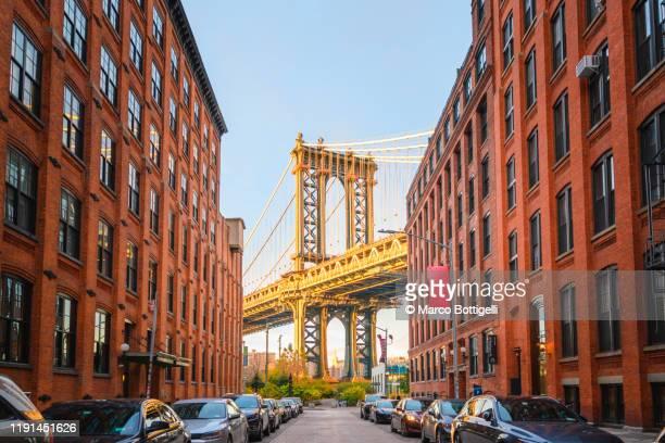 manhattan bridge at sunset seen from dumbo, brookyn, new york city - brooklyn new york stock-fotos und bilder