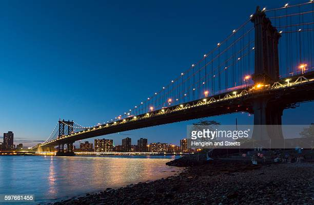 Manhattan bridge from riverbank at night, New York, USA