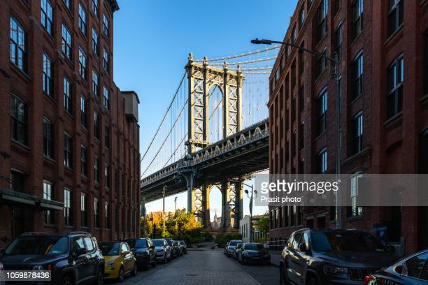 Manhattan bridge seen from a narrow alley enclosed by two brick buildings in New York, USA.