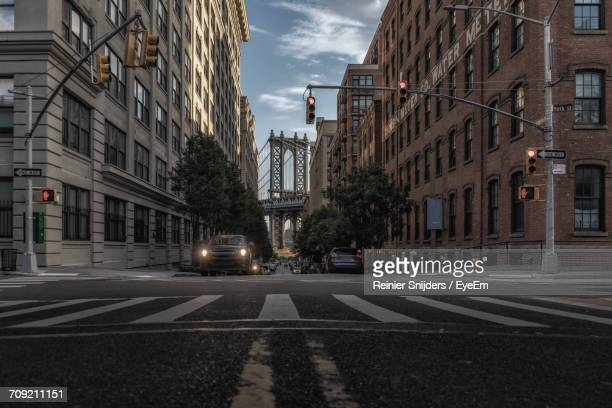manhattan bridge seen through buildings in city - lower east side manhattan stock pictures, royalty-free photos & images