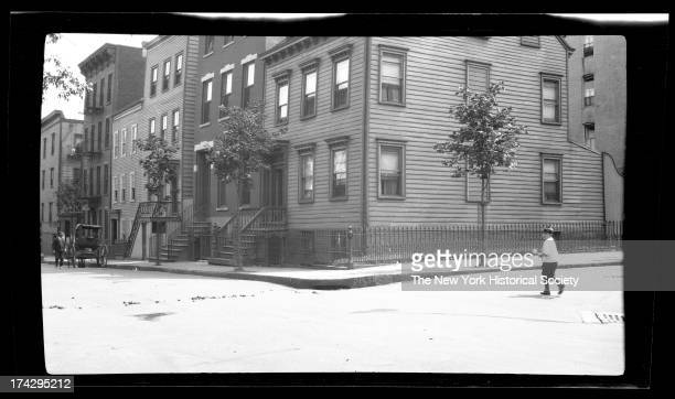 Unidentified residential intersection, with little boy crossing the street and a horse-drawn cariage at the far left, New York, New York, late 19th...