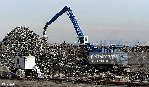 Manhattan can be seen in the background as a crane moves World Trade Center debris at the Fresh Kills Landfill 14 January 2002 Crews at ground zero...