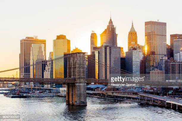 Manhattan Financial District and Brooklyn bridge during sunset, New York City, US