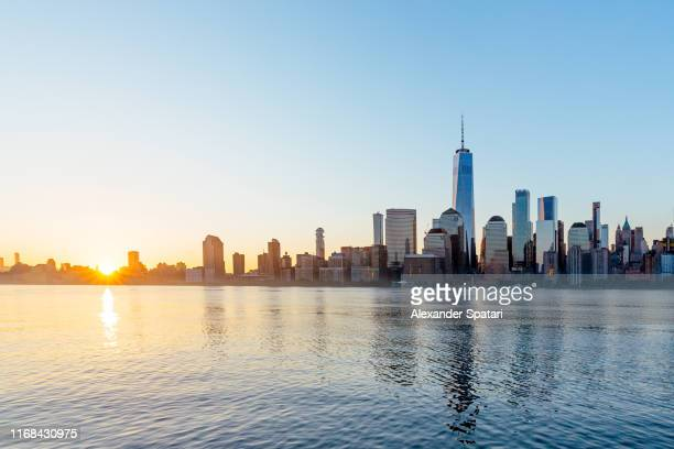 manhattan financial district skyline seen from jersey city at sunrise, usa - ウォール街 ストックフォトと画像
