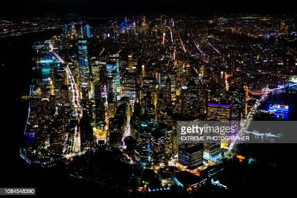 manhattan island and one world trade center as viewed from a helicopter above the hudson river at nighttime - world financial center new york city stock pictures, royalty-free photos & images
