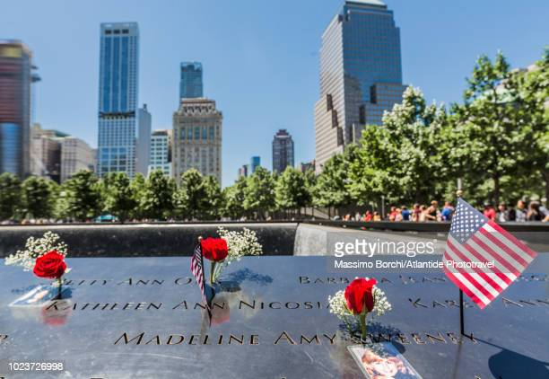 manhattan, lower manhattan, national september 11 memorial & museum, the south pool with the names of the victims and the american flag - 911 remembrance stock pictures, royalty-free photos & images