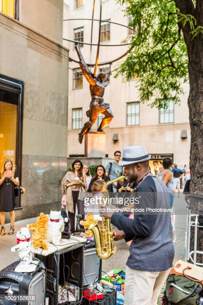 Manhattan, Midtown Manhattan, a street concert in the Fifth (5th) Avenue, the Atlas Statue from the Rockefeller Center on the background