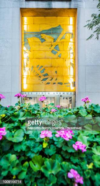 """manhattan, midtown manhattan, fifth (5th) avenue, flowers and the attilio piccirilli's glass block bas-relief, """"youth leading industry"""" over the fifth avenue entrance to the north wing of the international building at 636 fifth avenue - インターナショナルビル ストックフォトと画像"""