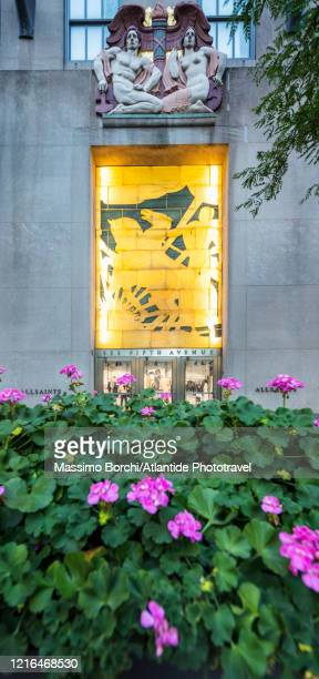 """manhattan, midtown manhattan, fifth (5th) avenue, flowers and the attilio piccirilli's glass block bas-relief, """"youth leading industry"""" - インターナショナルビル ストックフォトと画像"""