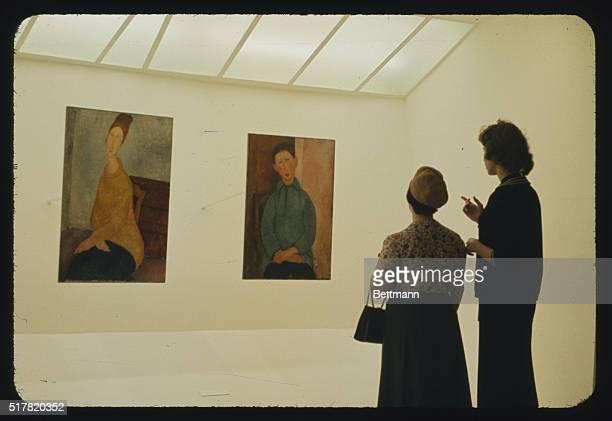 Manhattan New York New York Guggenheim Museum Visitors view paintings of Amadeo Modigliani's Yellow Sweater and Boy in Blue