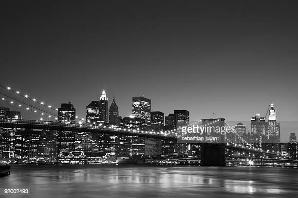 manhattan skyline at dusk with brooklyn bridge in front back&white