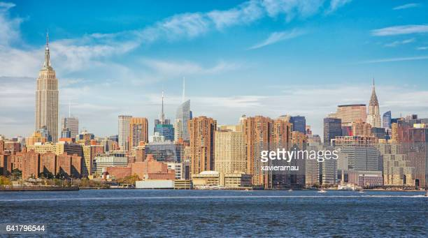 Manhattan skyline by East river against sky