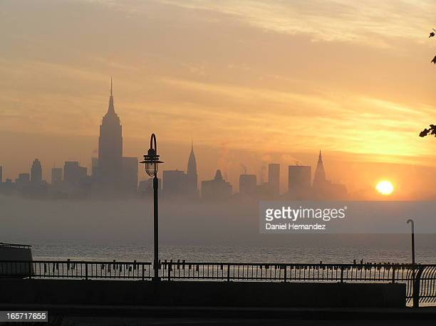 CONTENT] Manhattan skyline from New Jersey with fog rising over the Hudson River buildings silhouetted by a sunrise