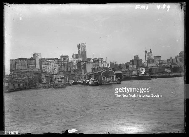 Manhattan skyline from the East River, showing 60 Wall Street and Piers 12 and 14, New York, New York, late 19th or early 20th century.