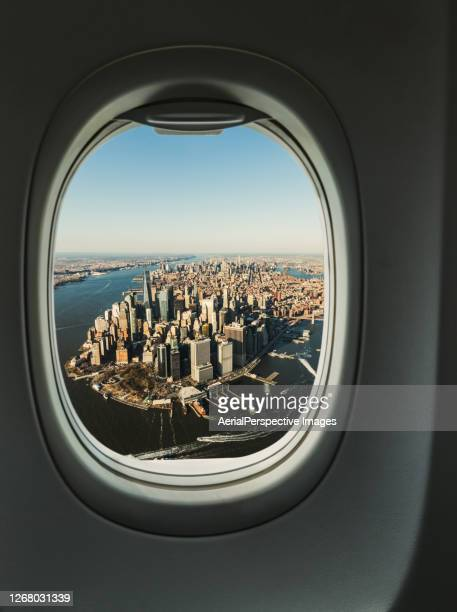 manhattan skyline from the porthole of aircraft, aerial view - new york city stock pictures, royalty-free photos & images