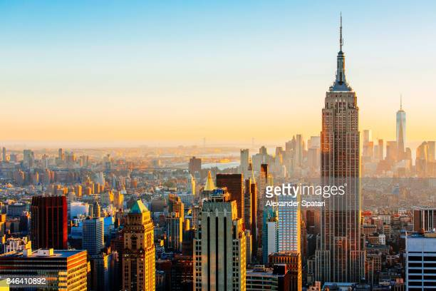 manhattan skyline on a sunny day empire state building on the right, new york, united states - orizzonte urbano foto e immagini stock