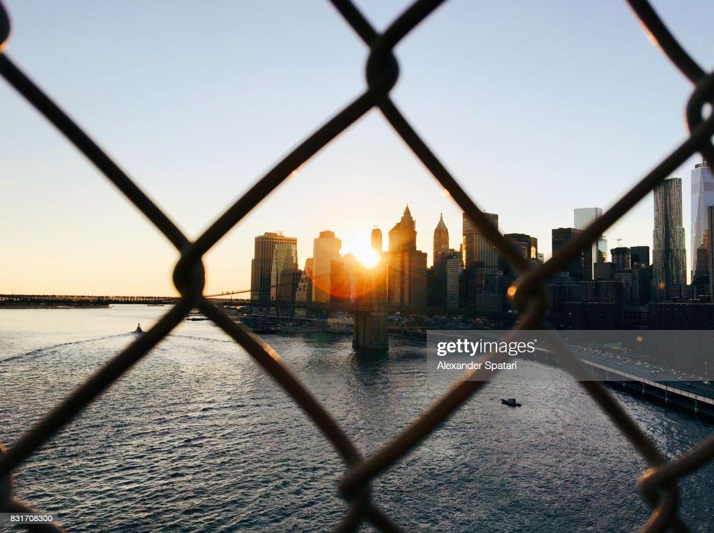 Manhattan skyline seen through a chainlink fence : Stock Photo