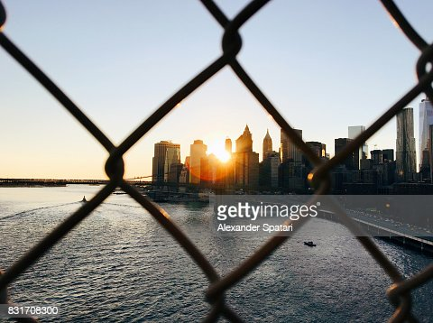 Manhattan skyline seen through a chainlink fence