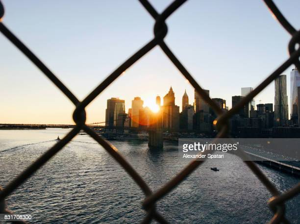 manhattan skyline seen through a chainlink fence - obstruir - fotografias e filmes do acervo
