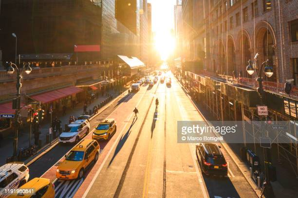manhattanhenge on the streets of new york city - new york city stock pictures, royalty-free photos & images