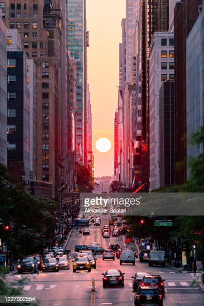 manhattanhenge seen from 42nd street in new york city, usa - manhattan new york city stock pictures, royalty-free photos & images