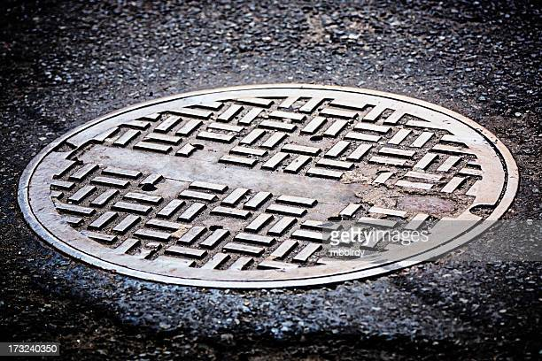 manhole cover on street - covering stock pictures, royalty-free photos & images