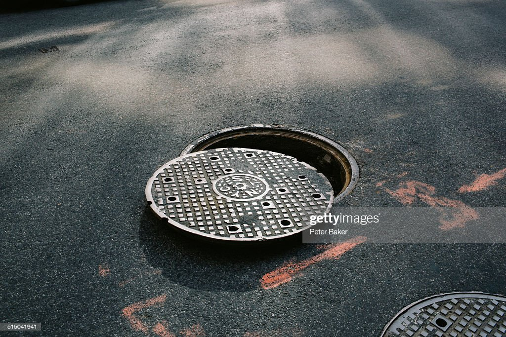 A manhole cover partially removed, close-up : Stock Photo