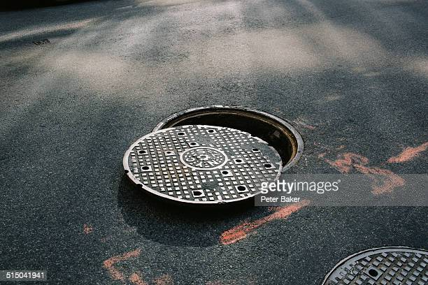 a manhole cover partially removed, close-up - lid stock photos and pictures