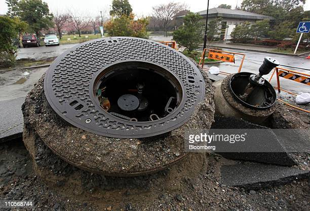 Manholes sit pushed up from the ground from the recent earthquake in Urayasu Japan on Tuesday March 22 2011 The quake caused water to bubble up from...