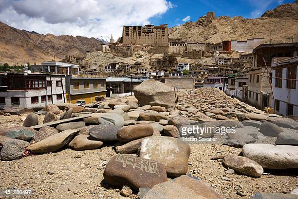 Mani Stone wall in Leh . In the back, the Leh Palace dominates the city. Mani stones are stones carved with a Tibetan Buddhist mantra or prayer. They...
